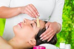 A cara da mulher do close up que recebem os pêlos faciais que enceram o tratamento, a mão usando a vara de madeira para aplicar a Imagem de Stock Royalty Free