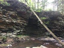 Cara da rocha na frente do córrego fotografia de stock