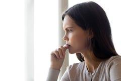 Cara da vista lateral da mulher séria que pensa sobre o problema fotografia de stock