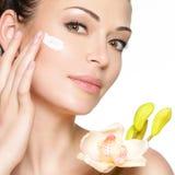Cara de la belleza de la mujer con crema cosmética en cara imagen de archivo libre de regalías