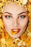 Cara de la belleza de la mujer con el unhealth que come las patatas fritas ru de los alimentos de preparación rápida Imagenes de archivo