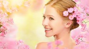 Cara de la belleza de la mujer hermosa joven con las flores rosadas en su ha imagenes de archivo