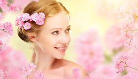 Cara de la belleza de la mujer hermosa joven con las flores rosadas en su ha foto de archivo