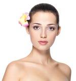 Cara de la belleza de la mujer joven con la flor Concepto del tratamiento de la belleza Imagen de archivo libre de regalías
