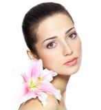 Cara de la belleza de la mujer joven con la flor Concepto del tratamiento de la belleza Foto de archivo libre de regalías