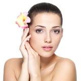 Cara de la belleza de la mujer joven con la flor Concepto del tratamiento de la belleza Fotografía de archivo