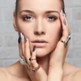 Cara de la belleza Manos del ` s de la mujer con los anillos de la joyería Fotografía de archivo
