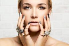 Cara de la belleza manos del ` s de la mujer con joyería Imagenes de archivo