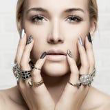 Cara de la belleza manos del ` s de la mujer con joyería Fotografía de archivo libre de regalías