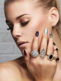 Cara de la belleza Manos del ` s de la mujer con los anillos de la joyería Foto de archivo