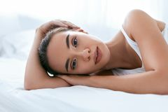 Cara de la belleza Mujer hermosa con la piel sana en la cama blanca fotos de archivo libres de regalías