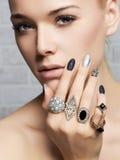 Cara de la belleza woman& x27; manos de s con los anillos de la joyería Imágenes de archivo libres de regalías