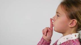Cara de la chica joven en el perfil que pone el finger a los labios que hacen para silenciar gesto metrajes