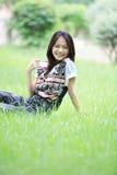 Cara de la emoción de relajación de la mujer asiática que se sienta en g Imágenes de archivo libres de regalías
