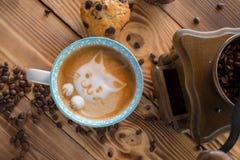 Cara de la espuma del gato del café del arte del latte en taza con los granos y las galletas dispersados de café en la tabla de m Fotografía de archivo