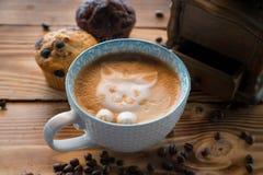 Cara de la espuma del gato del café del arte del latte en taza con los granos y las galletas dispersados de café en la tabla de m Fotografía de archivo libre de regalías