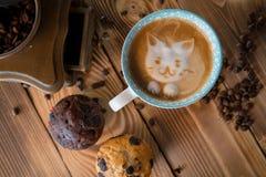 Cara de la espuma del gato del café del arte del latte en taza con los granos y las galletas dispersados de café en la tabla de m Fotos de archivo