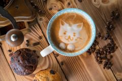 Cara de la espuma del gato del café del arte del latte en taza con los granos y las galletas dispersados de café en la tabla de m Imagen de archivo