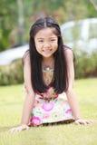 Cara de la muchacha asiática con el pelo largo que se sienta en campo de hierba verde Fotografía de archivo libre de regalías
