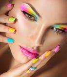Cara de la muchacha con maquillaje vivo y esmalte de uñas colorido imágenes de archivo libres de regalías