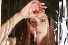 Cara de la muchacha detrás del vidrio Fotografía de archivo
