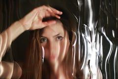 Cara de la muchacha detrás del vidrio Fotos de archivo libres de regalías