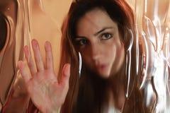 Cara de la muchacha detrás del vidrio Fotografía de archivo libre de regalías