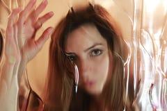 Cara de la muchacha detrás del vidrio Foto de archivo