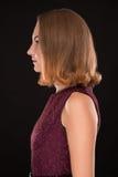 Cara de la muchacha elegante joven en perfil en fondo negro Imagen de archivo libre de regalías