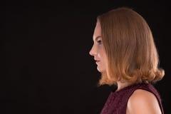 Cara de la muchacha elegante joven en perfil en fondo negro Imagenes de archivo