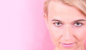 Cara de la muchacha en un fondo rosado Foto de archivo libre de regalías