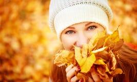 Cara de la muchacha feliz con las hojas de otoño en paseo Imagen de archivo