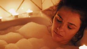 Cara de la muchacha morena joven en cuarto de ba?o con la luz de una vela de la espuma que descansa y que se relaja metrajes