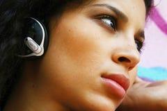 Cara de la muchacha que escucha el reproductor Mp3 Imagen de archivo libre de regalías