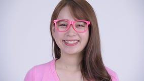 Cara de la mujer asiática feliz joven del empollón que cabecea la cabeza sí almacen de video