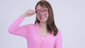 Cara de la mujer asiática feliz joven del empollón que juega con la lupa almacen de metraje de vídeo