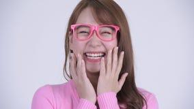 Cara de la mujer asiática feliz joven del empollón que parece sorprendida almacen de metraje de vídeo