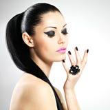 Cara de la mujer hermosa con los clavos negros y los labios rosados Imagen de archivo libre de regalías