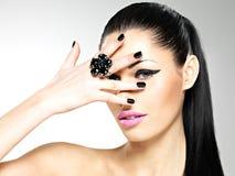 Cara de la mujer hermosa con los clavos negros y los labios rosados Fotos de archivo libres de regalías