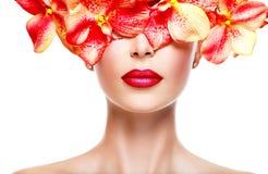 Cara de la mujer con el lápiz labial brillante en labios y flores rosadas Imagen de archivo libre de regalías