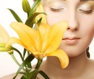 Cara de la mujer con la flor amarilla del lirio Imágenes de archivo libres de regalías