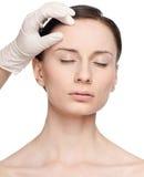 Cara de la mujer de la salud del tacto y del examen del Beautician. imagenes de archivo