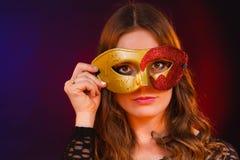 Cara de la mujer del primer con la máscara roja de oro del carnaval en oscuridad fotografía de archivo