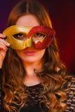 Cara de la mujer del primer con la máscara roja de oro del carnaval en oscuridad fotos de archivo libres de regalías