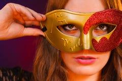 Cara de la mujer del primer con la máscara roja de oro del carnaval en oscuridad imágenes de archivo libres de regalías