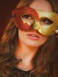 Cara de la mujer del primer con la máscara roja de oro del carnaval en oscuridad fotos de archivo