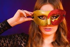 Cara de la mujer del primer con la máscara roja de oro del carnaval en oscuridad imagen de archivo