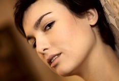 Cara de la mujer del primer en el fondo marrón del bokeh Imagen de archivo libre de regalías
