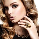 Cara de la mujer hermosa con joyería larga del pelo y del oro Imagenes de archivo