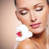 Cara de la mujer hermosa con una flor blanca de la orquídea Fotos de archivo